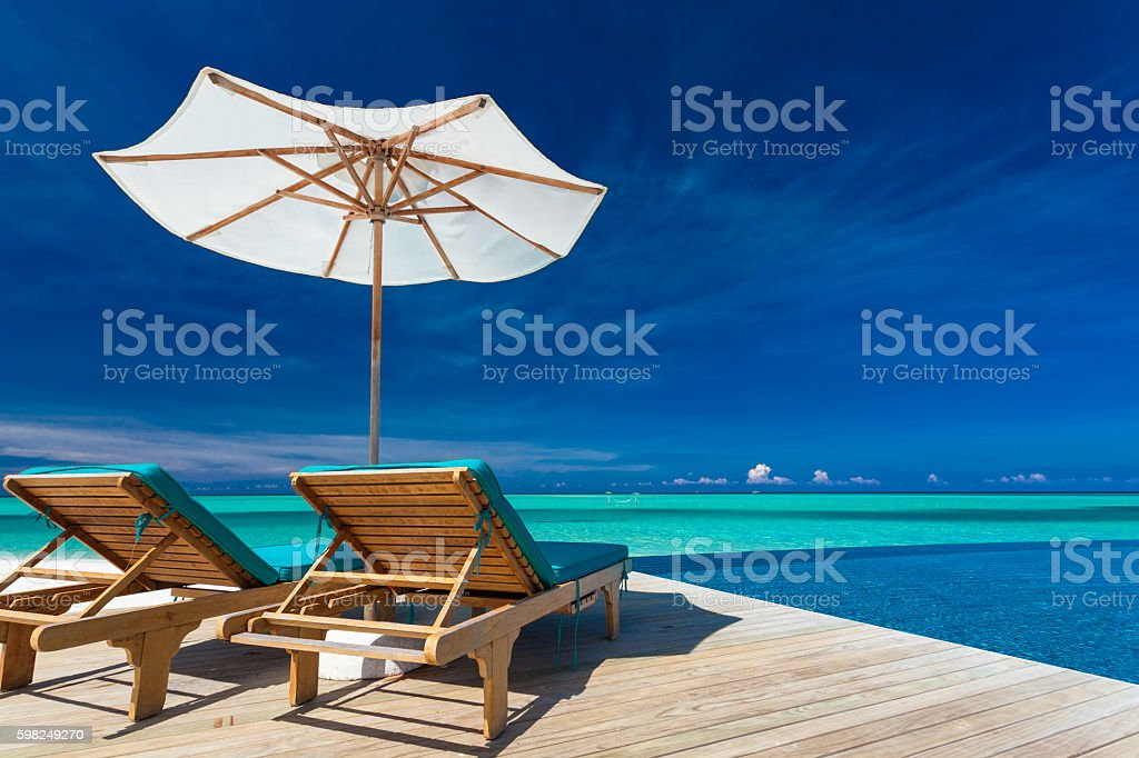 Deck chairs overlooking infinity pool and tropical lagoon stock photo