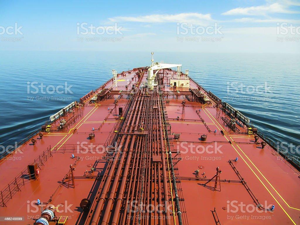 Deck of a crude oil carrier proceeding through blue ocean. stock photo