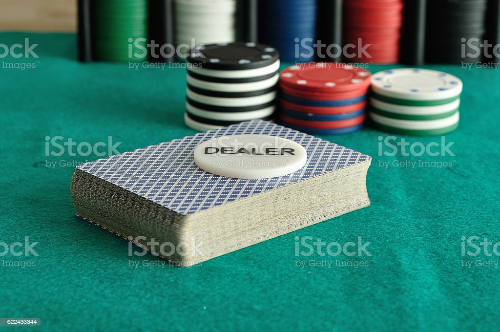 Deck of card with the dealer chip and poker chips stock photo