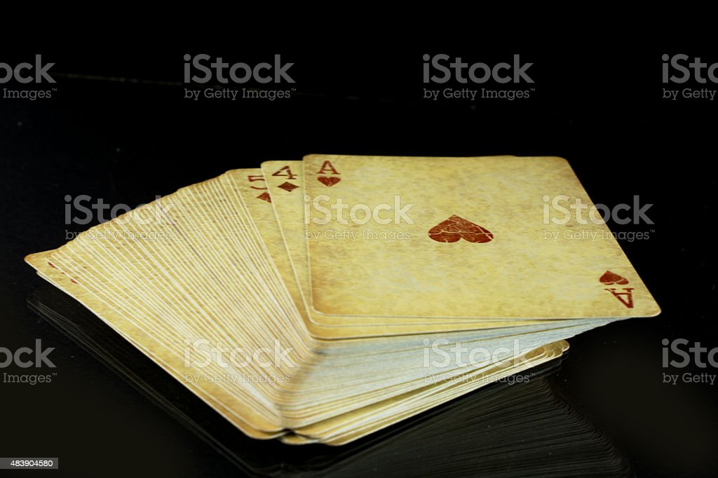 Deck of old worn playing cards on black stock photo