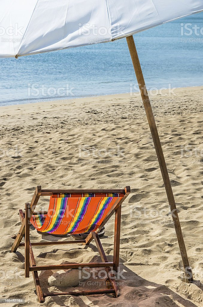 Deckchair and Parasol on a solitary Beach royalty-free stock photo
