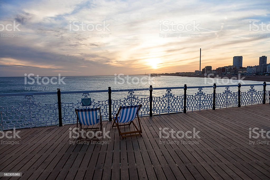 Deckchairs by the sea on pier at sunset stock photo