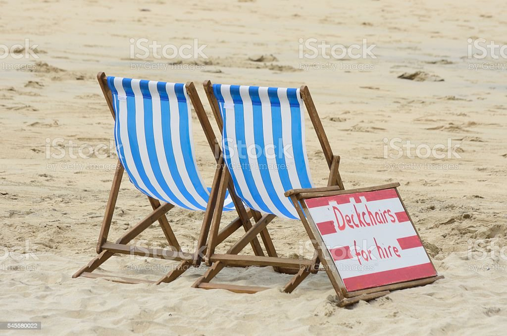 Deckchairs for Hire on beach stock photo
