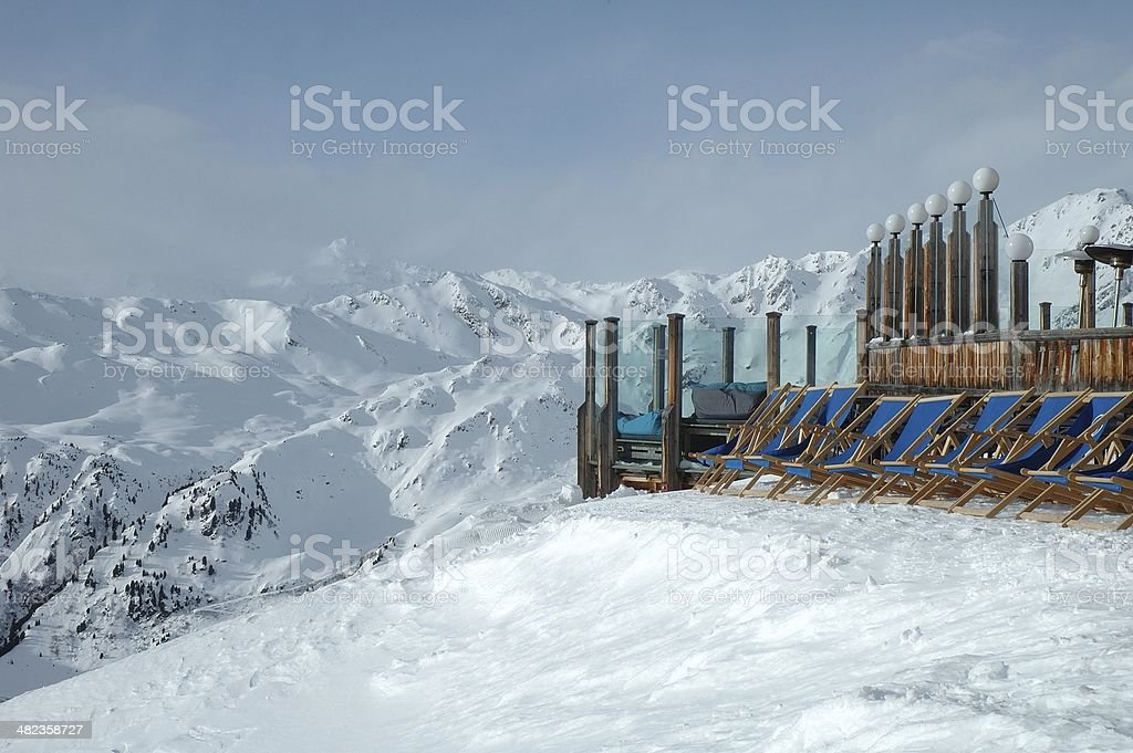 Deckchairs standing on peak in Alps in winter stock photo