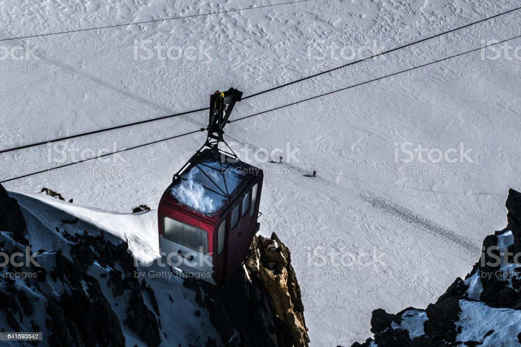 Decommisioned cable car hanging from cables over skiers traversing glacier below on trodden path. stock photo