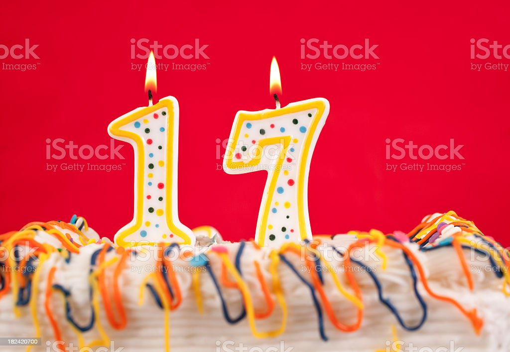 Decorated birtday cake with number 17 candles.  Red background royalty-free stock photo