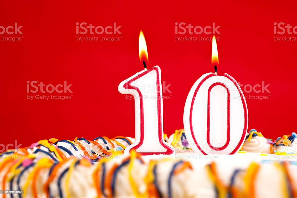 Decorated birthday cake with number 10 candles. Red background.