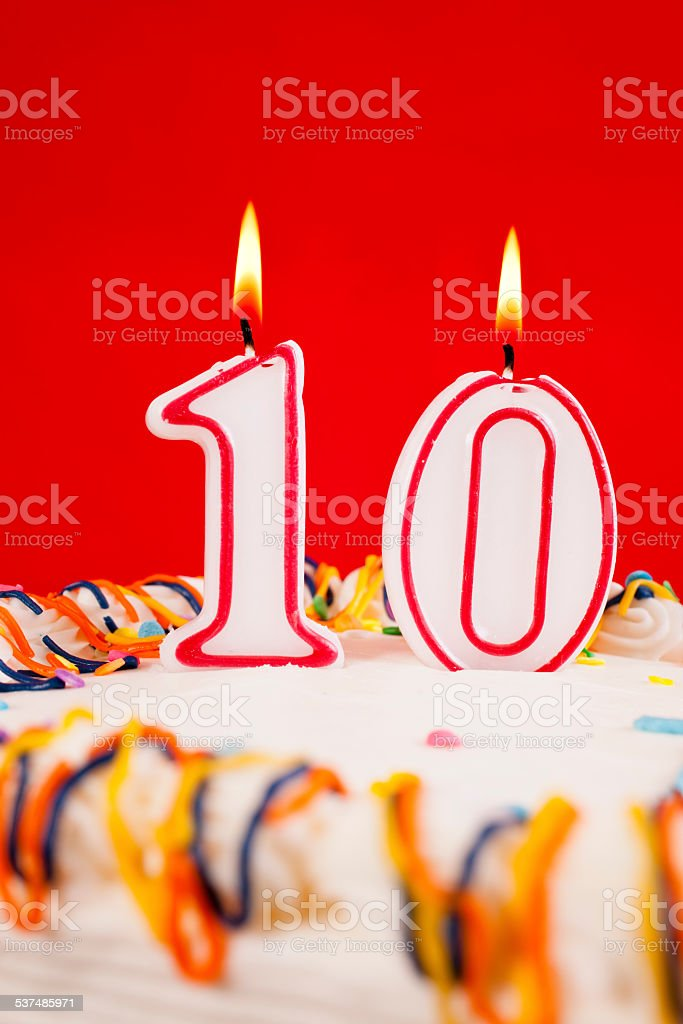 Decorated birthday cake with number 10 burning candles. Red...