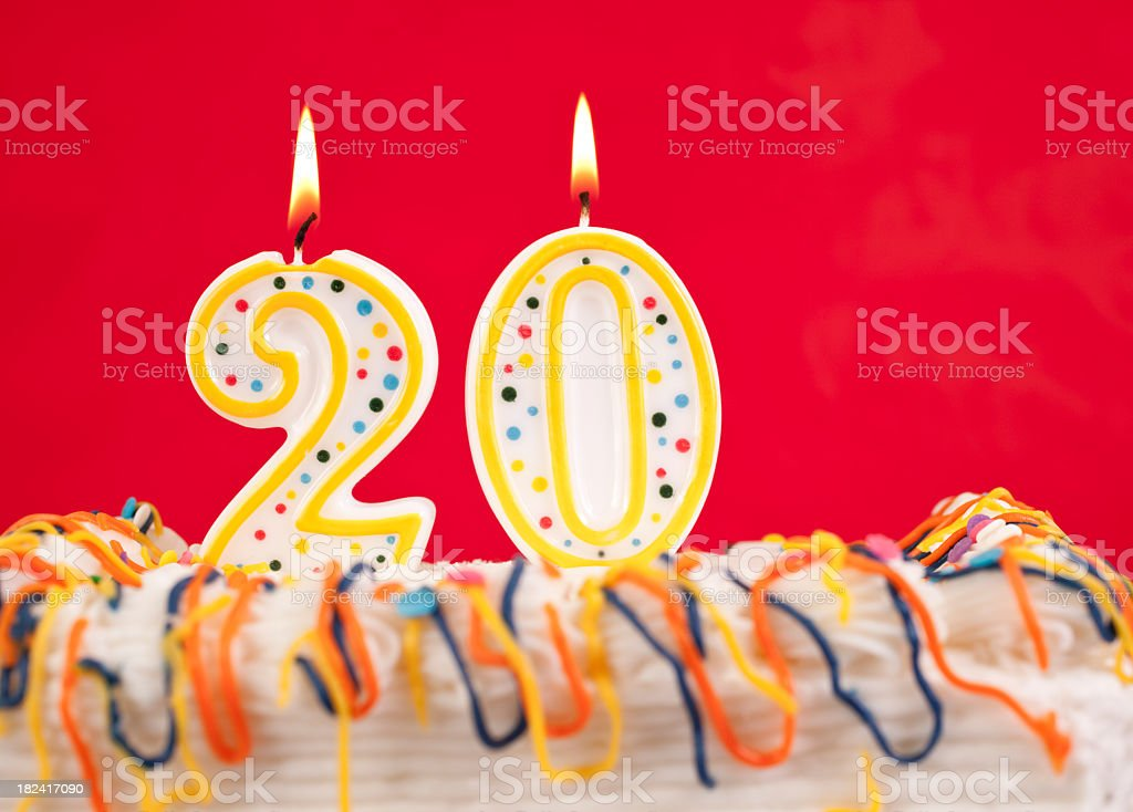 Decorated birthday cake with number 20 buring candles.  Red background. royalty-free stock photo
