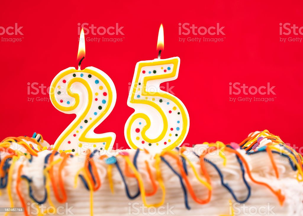 Decorated birthday cake with number 25 burning candles. Red background. royalty-free stock photo