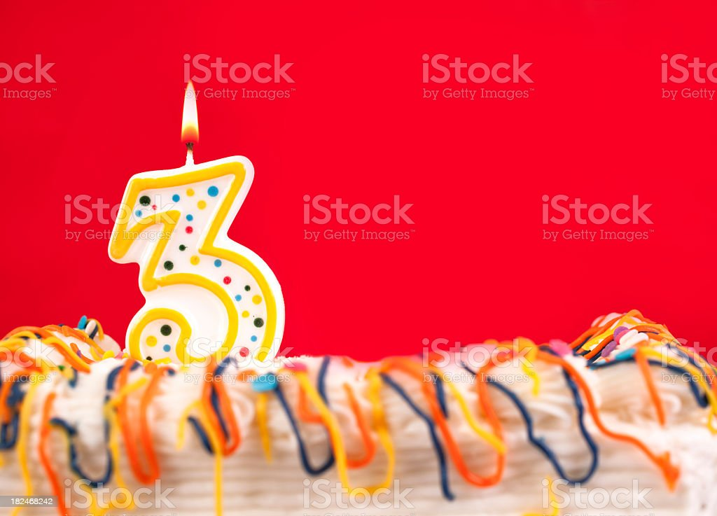 Decorated birthday cake with number 3 burning candle. Red background. royalty-free stock photo