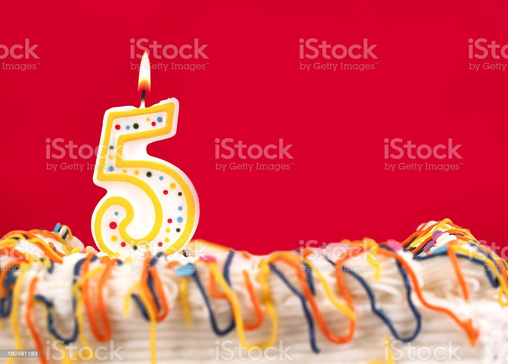 Decorated birthday cake with number 5 burning candle. Red background. stock photo