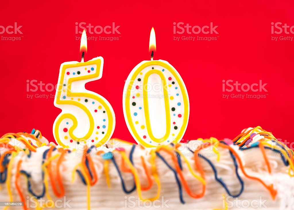 Decorated birthday cake with number 50 burning candles. Red background. royalty-free stock photo