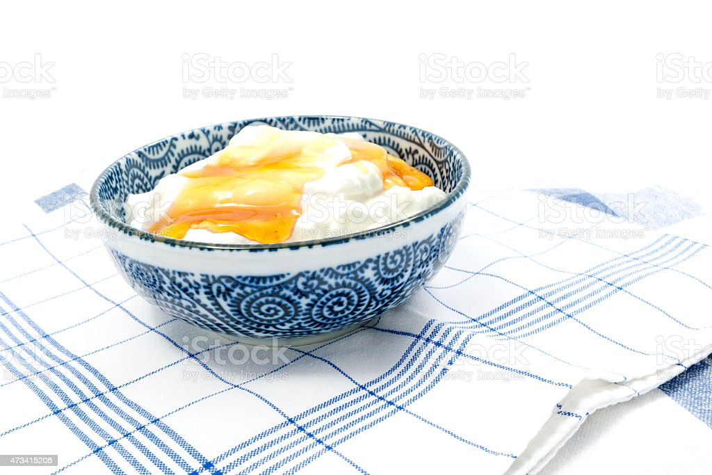 Decorated bowl with white greek yogurt and golden honey stock photo
