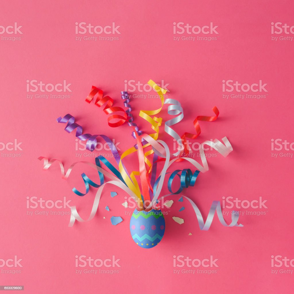 Decorated Easter egg with party streamers on pink background. Easter concept. Flat lay. stock photo