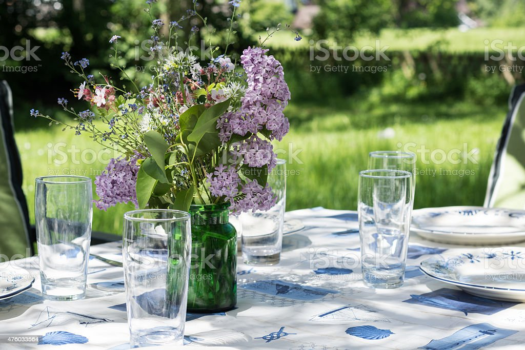 decorated garden table to eat outside in the early summer stock photo