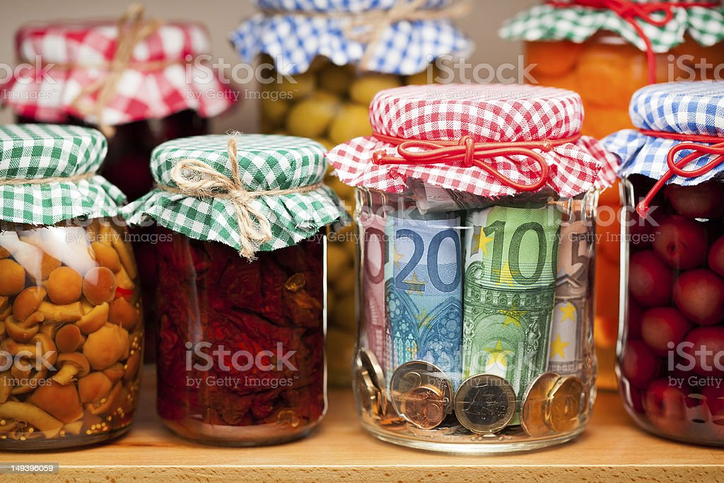 A decorated jar of money amongst other jarred foods royalty-free stock photo