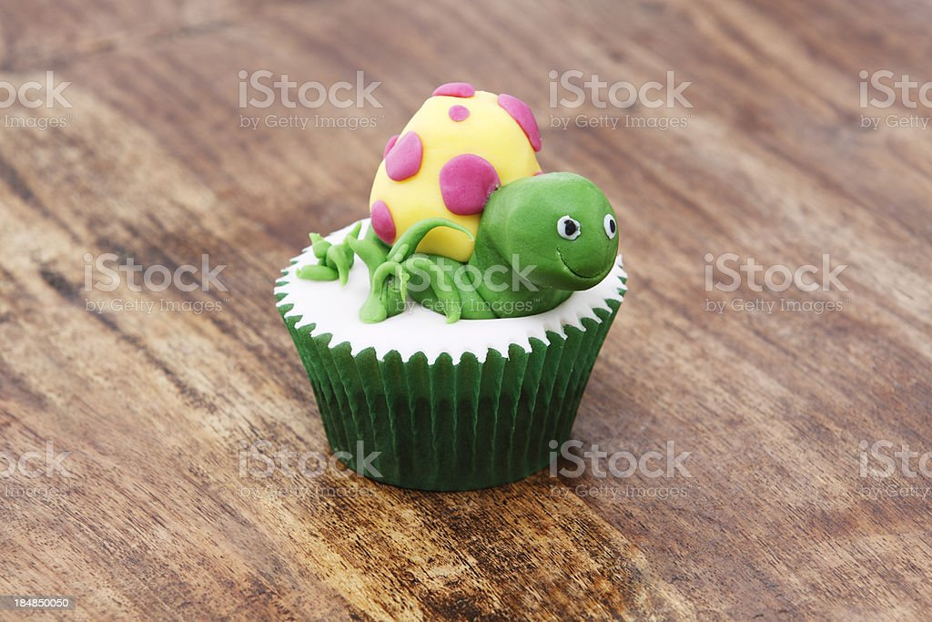 Decorated Turtle Cupcake on Wooden Background stock photo