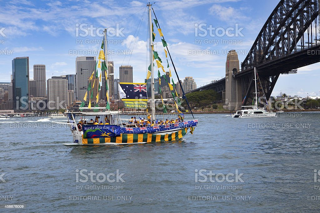 Decorated yacht sails under Sydney Harbour Bridge on Australia Day royalty-free stock photo