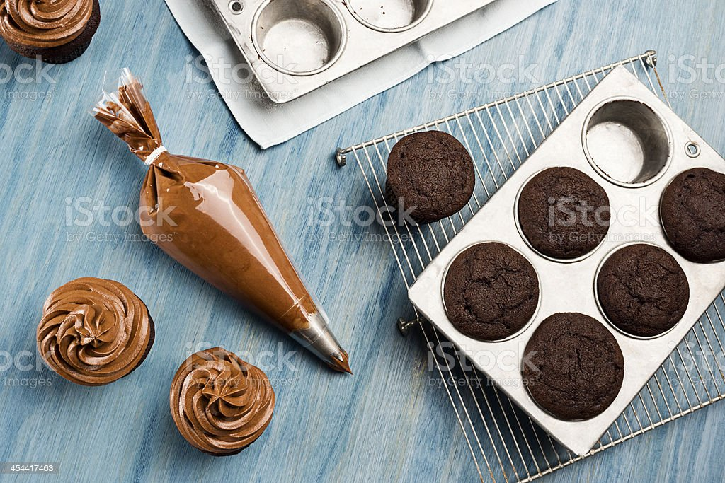 Decorating Chocolate Cupcakes with Frosting stock photo