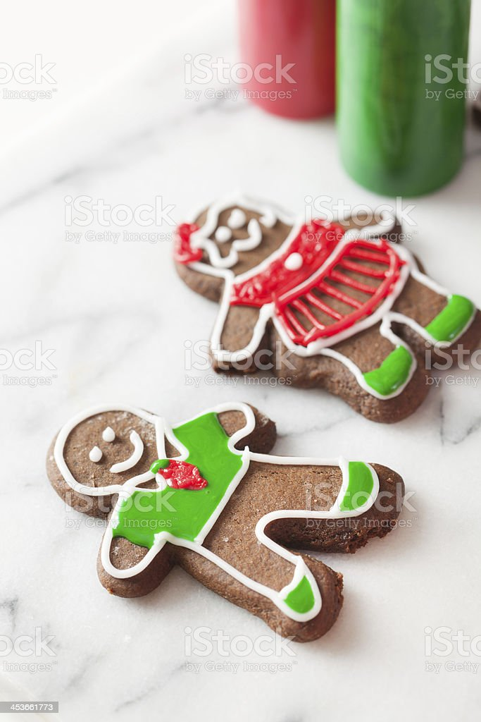 Decorating Christmas Cookies Gingerbread Couple with Frosting Close-up royalty-free stock photo