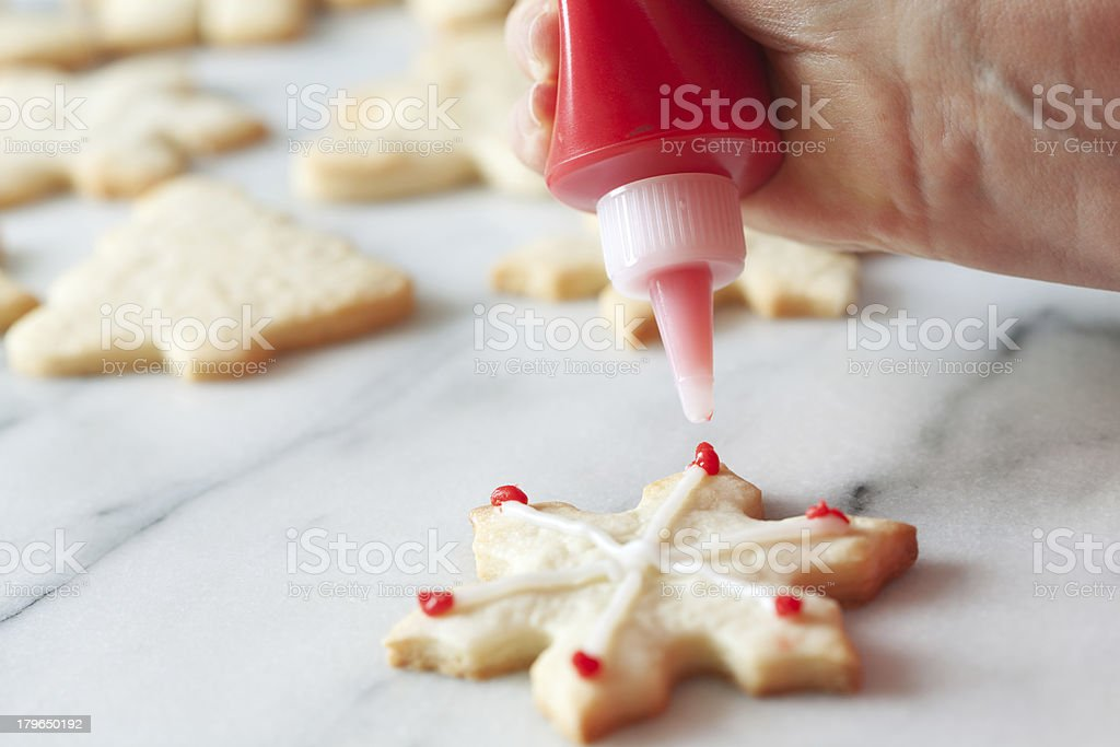 Decorating Christmas Snowflake Cookies with Sugar Frosting Hz royalty-free stock photo