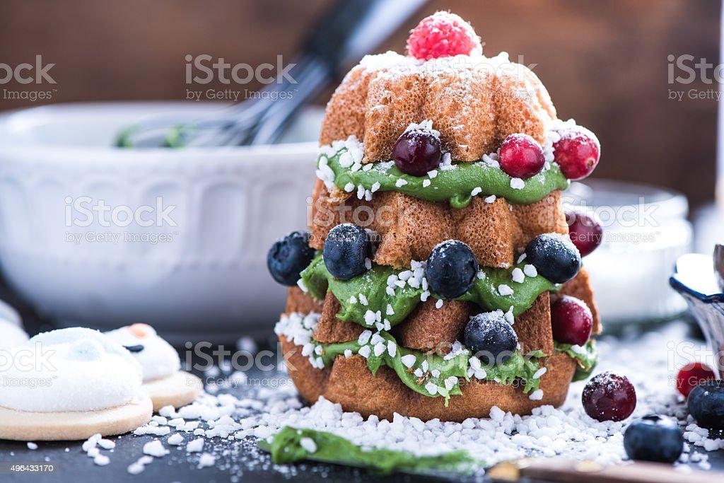 Decorating Christmas tree cake with fruits stock photo