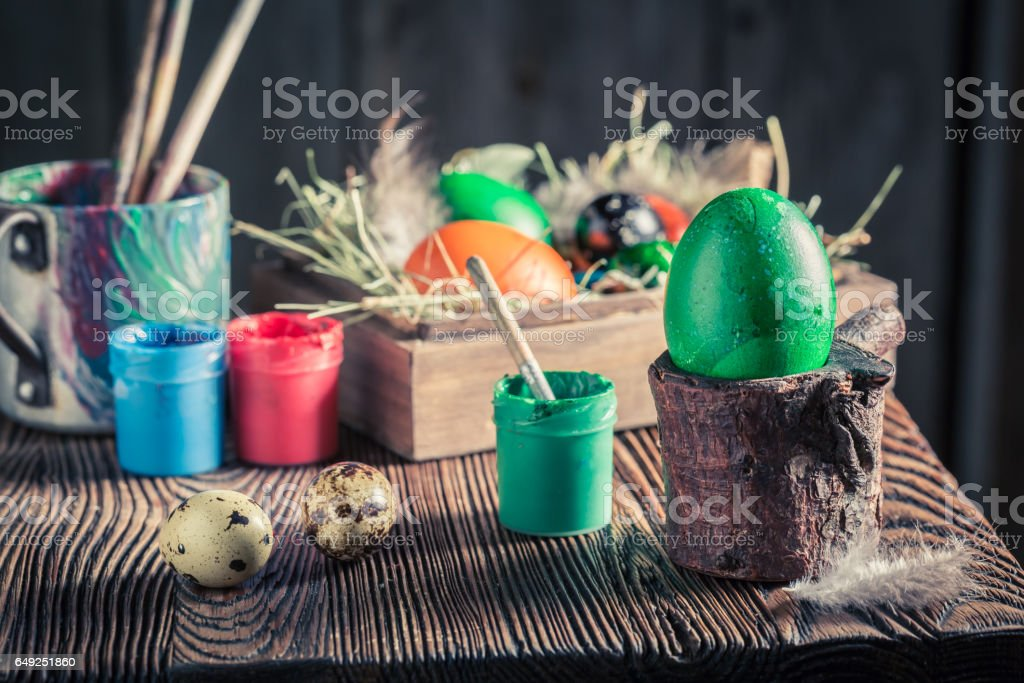 Decorating Easter eggs with hay and feathers stock photo