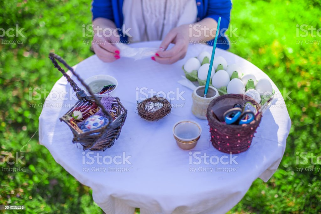Decorating easter eggs with paint and decoupage for holiday in the garden stock photo
