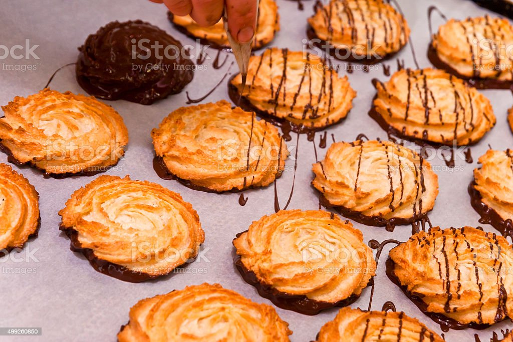 Decorating of coconut macaroons with chocolate stock photo
