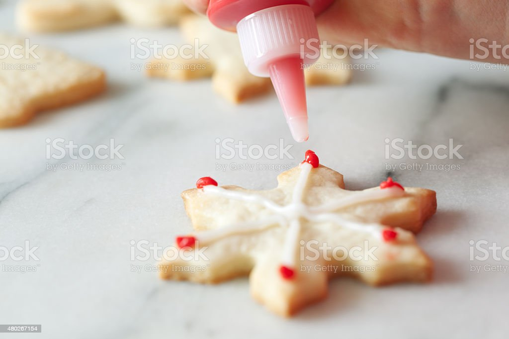 Decorating Snowflake Christmas Cookie with Frosting stock photo