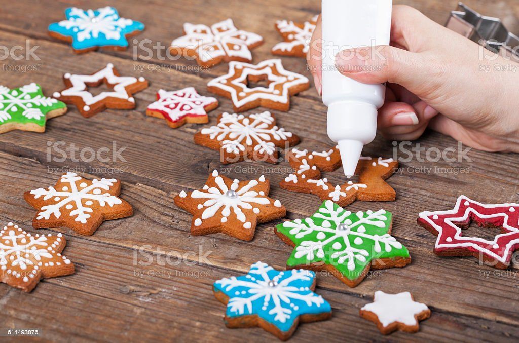 Decorating Star shaped Christmas gingerbread cookies with white icing stock photo