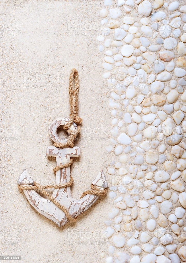 Decorative anchor on the sea sand stock photo