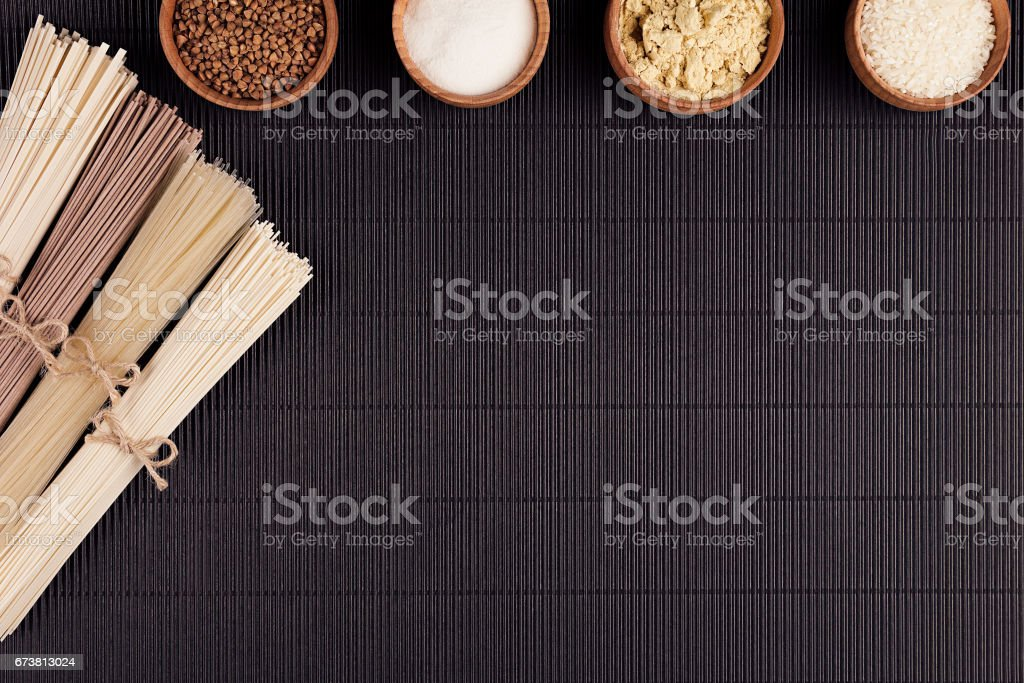 Decorative border of bundles raw noodles with ingredient in wooden bowls on black striped mat background with copy space, top view. stock photo