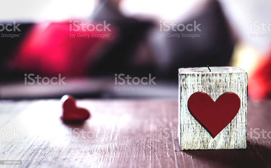 decorative candle with a heart on a table stock photo