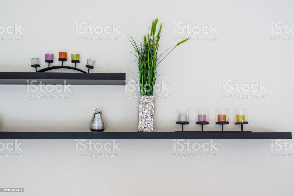 Decorative candle with flower vase on wooden shelf. stock photo