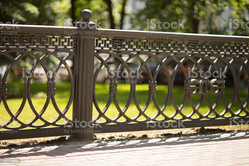 decorative fence on the background of vegetation stock photo
