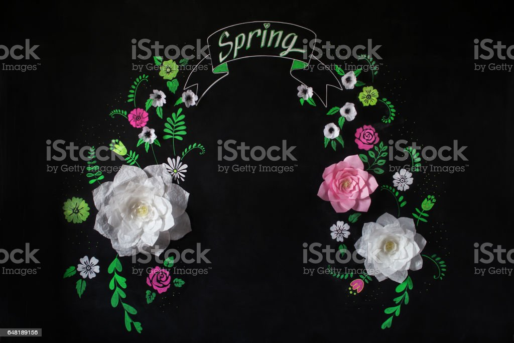 Decorative flowers from paper on a black background. Decorative frame from paper flowers. Drawing chalk on a black board stock photo