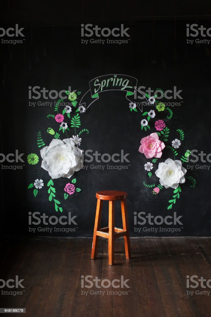Decorative flowers from paper on a black background. Decorative frame from paper flowers. Drawing chalk on a black board. stock photo
