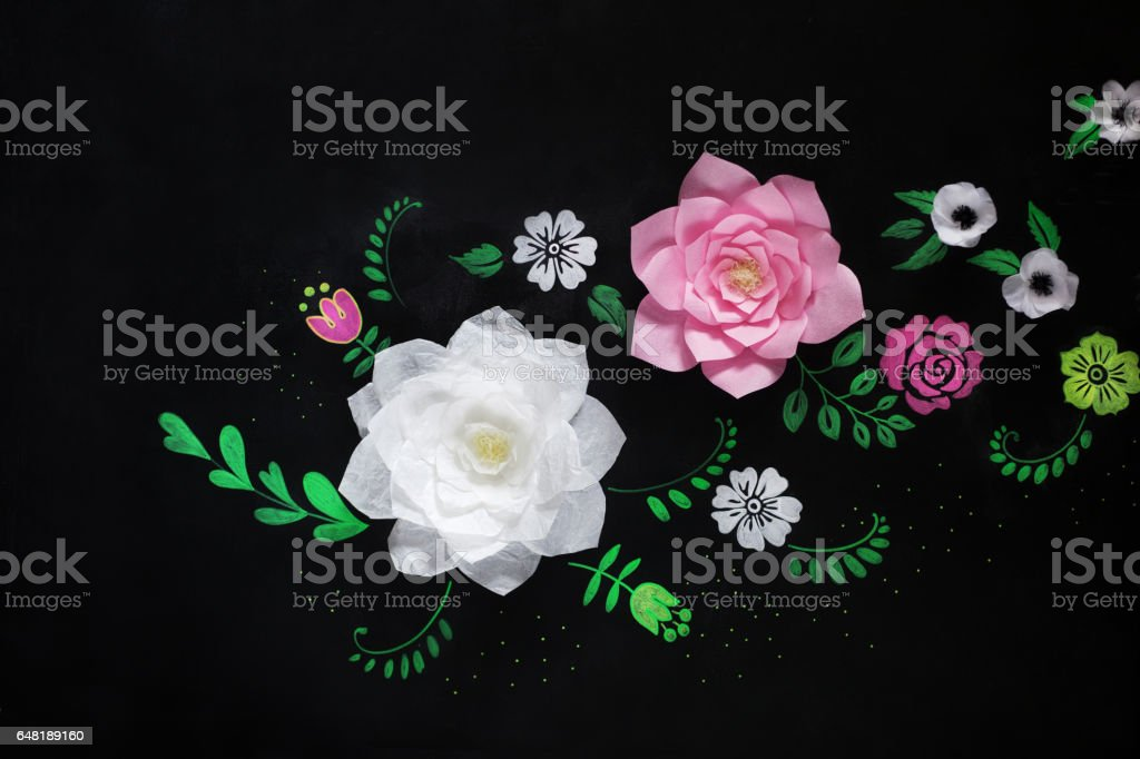Decorative flowers from paper on a black background.  Drawing chalk on a black board. stock photo