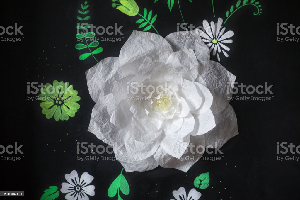 Decorative flowers from paper on a black background.  Drawing chalk on a black board. Soft focus stock photo