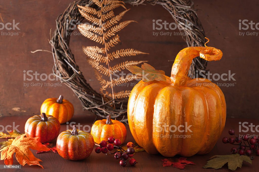 decorative golden papier-mache pumpkin and autumn leaves for hal stock photo
