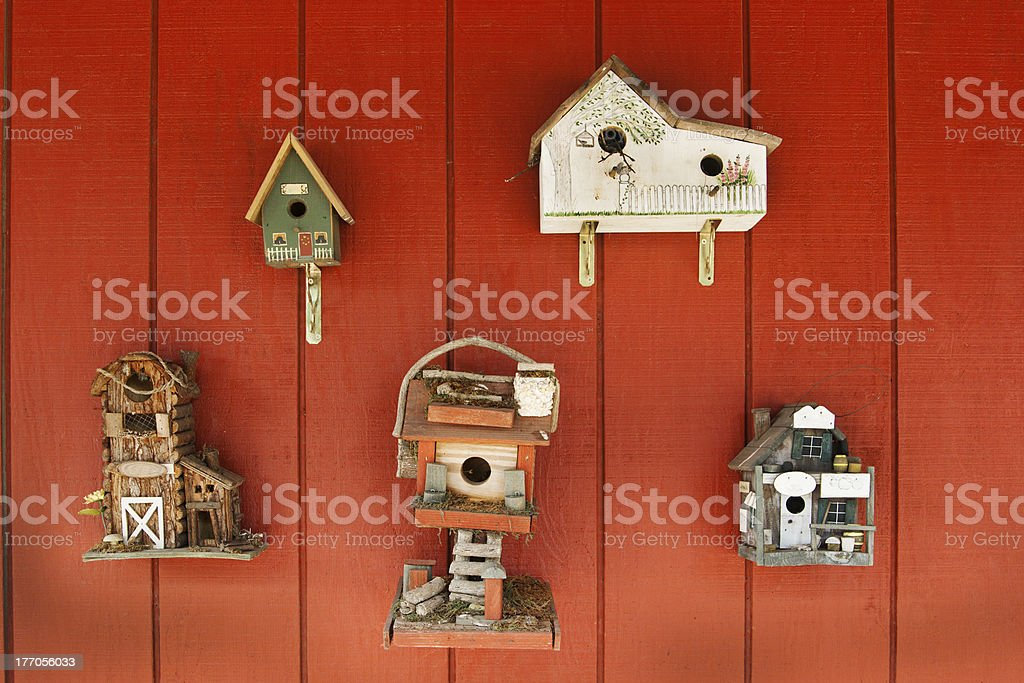 Decorative Variety of Architectural Birdhouses Hanging on Wooden Red Wall royalty-free stock photo