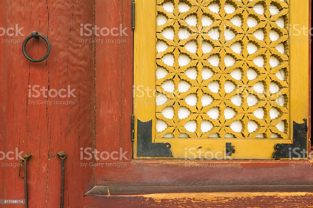 Decorative yellow shutter and red wood front stock photo