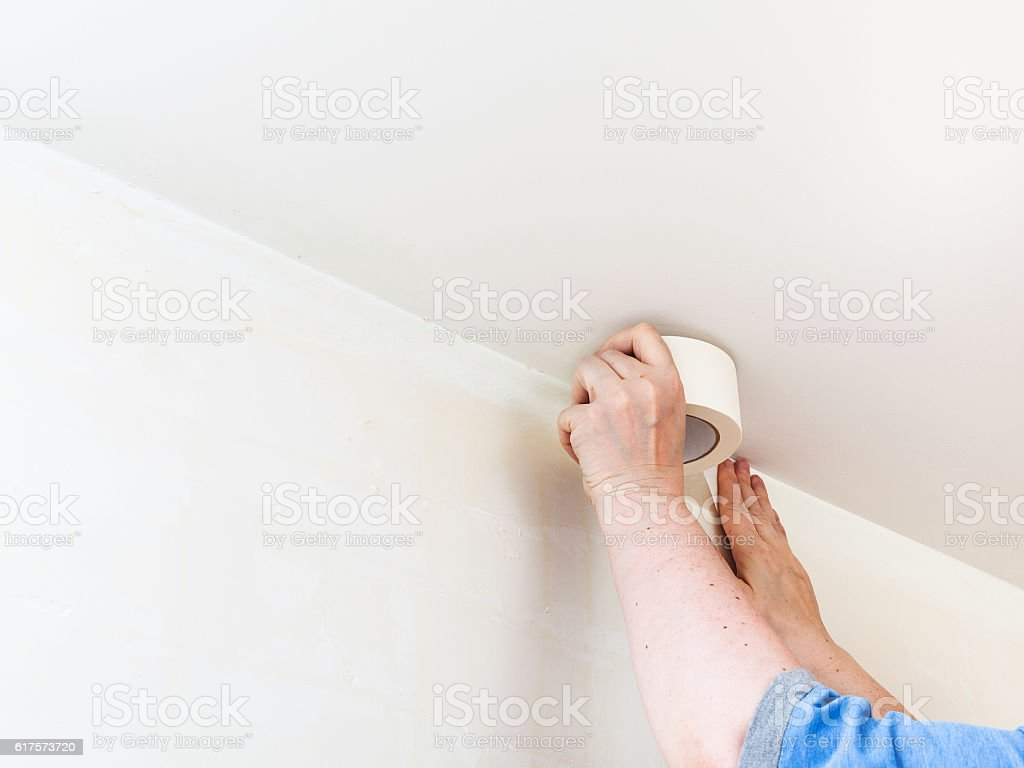 Decorator fixes tape on wall before painting stock photo
