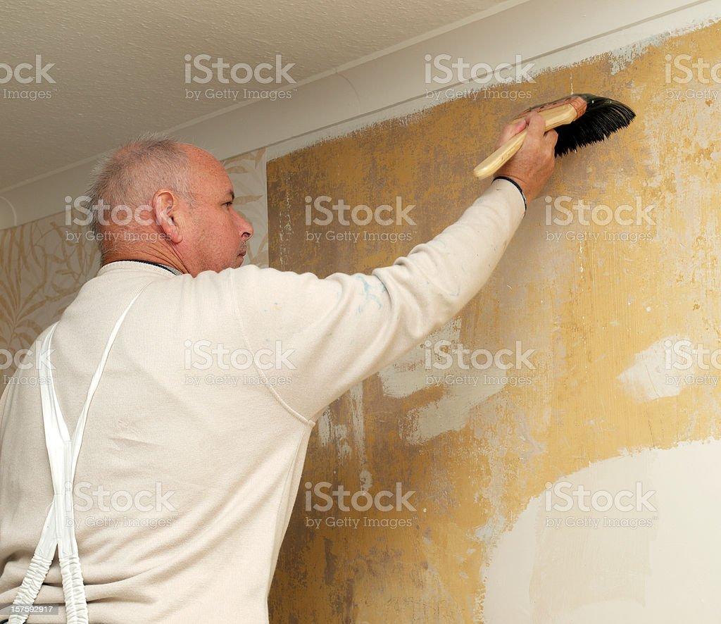 Decorator preparing wall prior to hanging wallpaper royalty-free stock photo