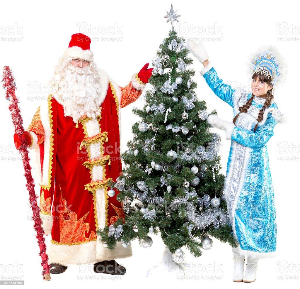 Ded Moroz and Snegurochka near Christmas tree stock photo