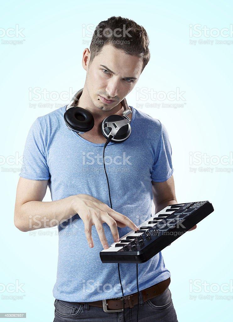 Deejay with headphones pressing keys on midi keyboard royalty-free stock photo