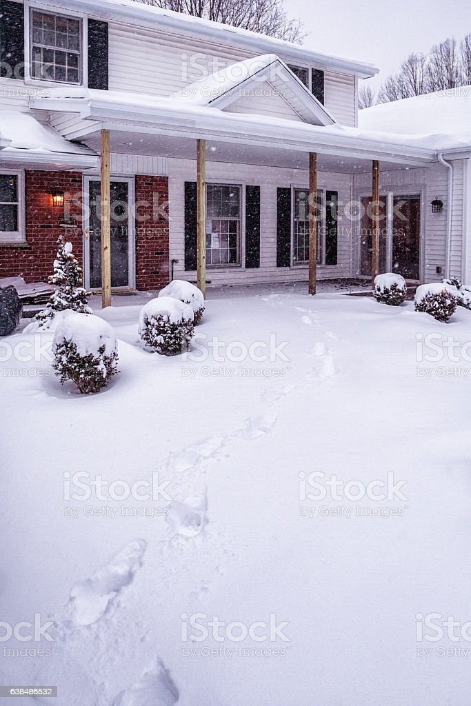Deep Blizzard Snow Footprints Leading to Warm Home Entrance stock photo