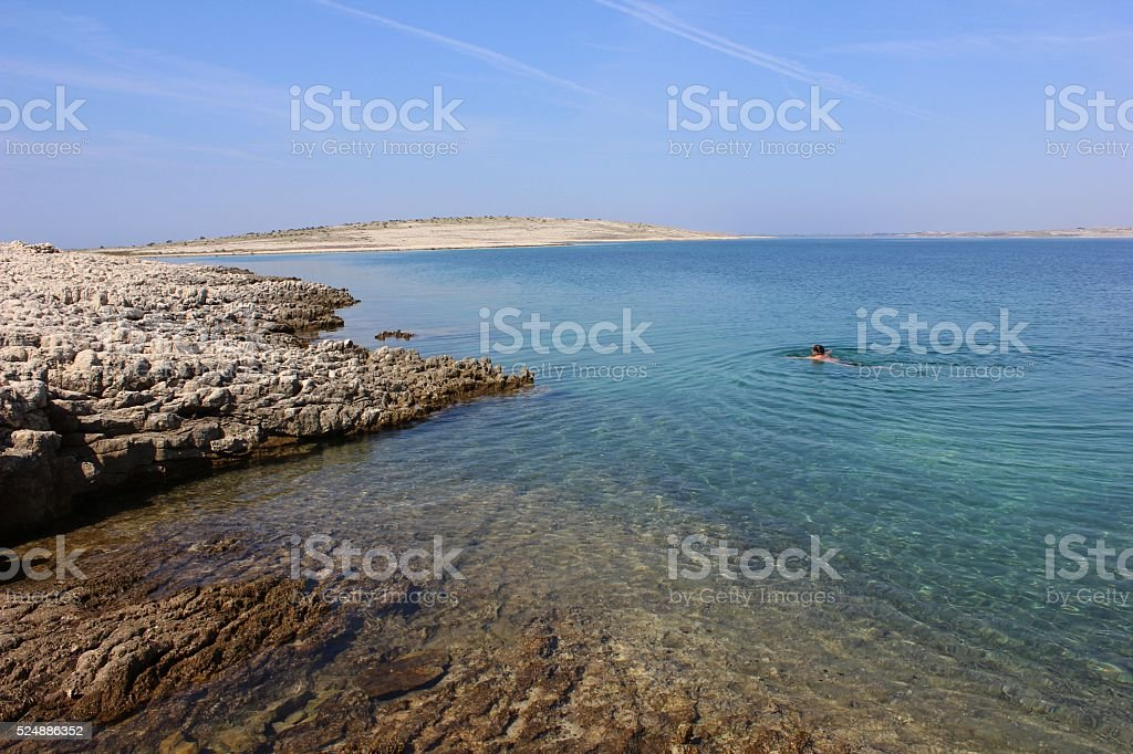 Deep blue sea with rocky bank and island and swimming person. stock photo